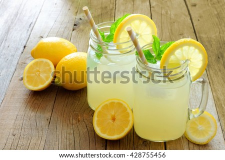Two mason jar glasses of homemade lemonade on a rustic wooden background - stock photo