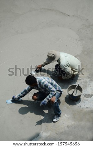 two mason leveling the cement screed under a hot sun