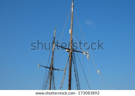 two masted schooner sail masts and rigging set against a beautiful blue sky - stock photo