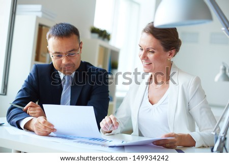 Two mature business partners discussing document in office - stock photo