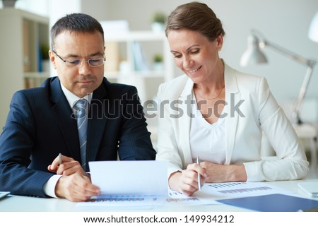 Two mature business partners looking at document in office - stock photo