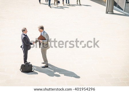 Two mature businessmen shaking hands outdoors - Managers having a deal after a conference meeting - stock photo