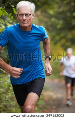 Two Mature Male Joggers Running Along Path - stock photo