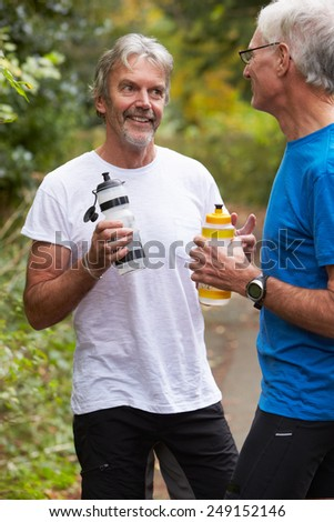 Two Mature Male Joggers Taking Break Whilst On Run - stock photo