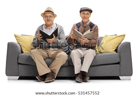 Two mature men with books sitting on a couch and looking at the camera isolated on white background
