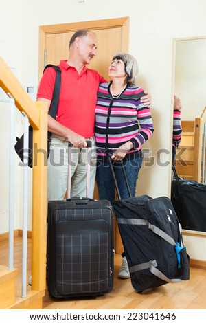 Two mature  tourists with luggage near door