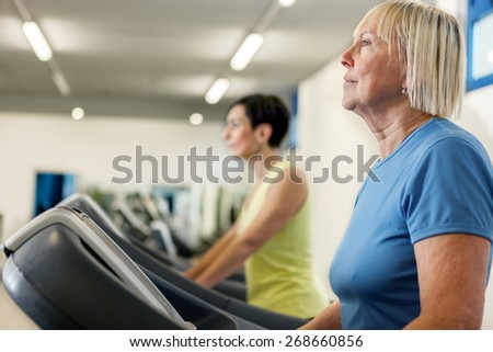 Two mature women are running on a treadmill in the fitness studio - stock photo
