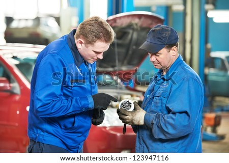 two mechanic engineers examining spare part of internal combustion engine of automobile car at repair service station - stock photo