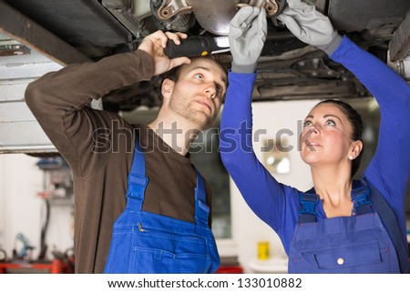 Two mechanics repairing or inspecting a car on hydraulic lift - stock photo