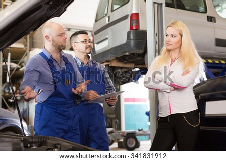 Two mechanics trying to cheat unhappy female client at workshop - stock photo
