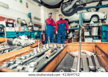 Two mechanics working on a car . close up on mechanic tools - stock photo