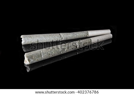 Two medical cannabis rolled joints on black background from side high angle - stock photo