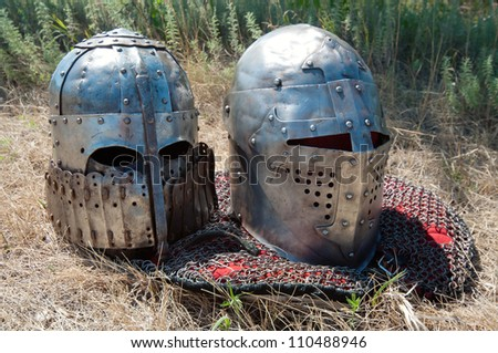 Two medieval knight's helmets on grass, horizontal shot - stock photo