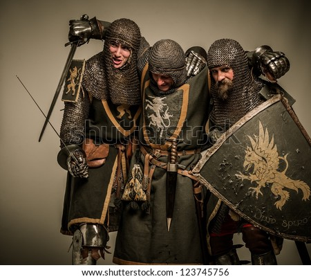 Two medieval knights carrying their buddy - stock photo