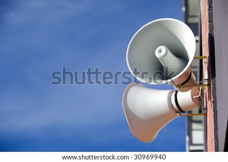 Two megaphone on the wall of a brick house on a background of blue sky - stock photo
