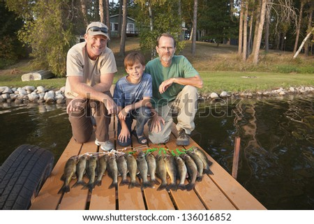 Two men and a boy pose with the day's catch of walleyes - stock photo