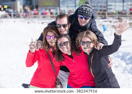 Two men and three women smiling at camera while standing outdoors in winter time. - stock photo