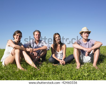 Two men and two women sitting together on the grass. Horizontal. - stock photo