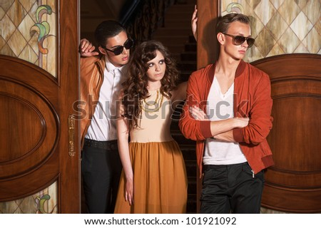 Two men and woman standing at the door - stock photo