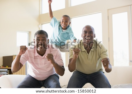 Two men and young boy in living room cheering and smiling - stock photo