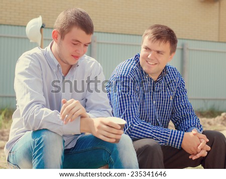 Two men, architects or engineers, taking a break for coffee on a building site sitting on wooden planks, one drinking a mug of coffee watching progress while the other chats - stock photo