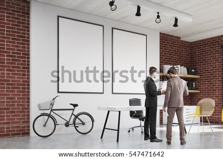 Two men are standing in a home office with a yellow transparent chair, a large white wall with two framed posters and a bicycle. Concept of a startup. 3d rendering. Mock up