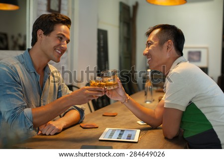 Two Men Cheers Toast Drink Ice Coffee, Asian Mix Race Friends Guys Happy Smile Sitting at Cafe Natural Light - stock photo