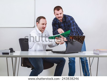 Two men discussing and pointing at computer and note book - stock photo