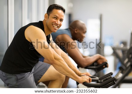 two men doing indoor biking in a fitness club - stock photo