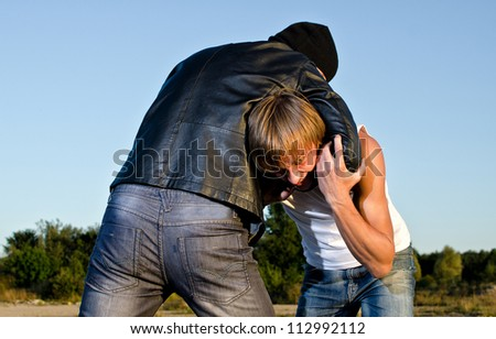 Two men fight outdoors. Robbery concept - stock photo