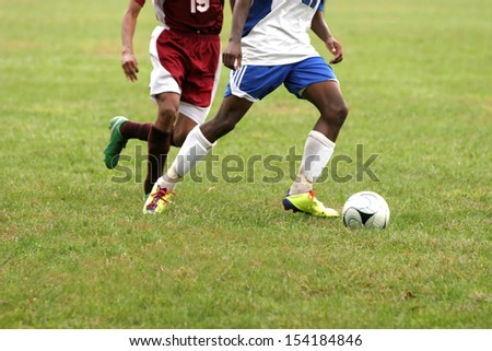 Two men fight over control of ball during a football game - stock photo