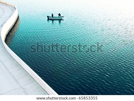 Two men fishing on a lake in a very contemporary urban setting. - stock photo