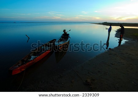 Two men fishing seaside  in the early morning. - stock photo