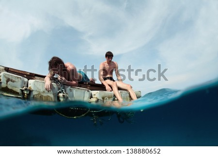 Two men floating in a sea on a plastic raft - stock photo