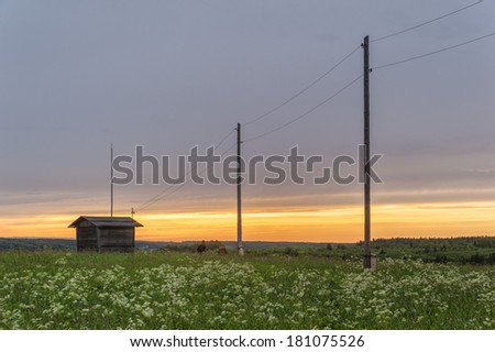 Two men goes along power line with wooden poles to barn against sunset background.