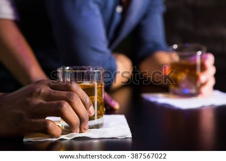 Two men having whiskey at bar counter in bar