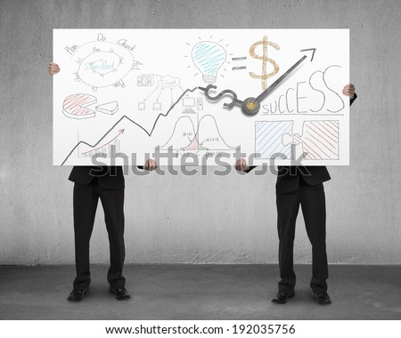 Two men holding board with clock hands and business doodles - stock photo