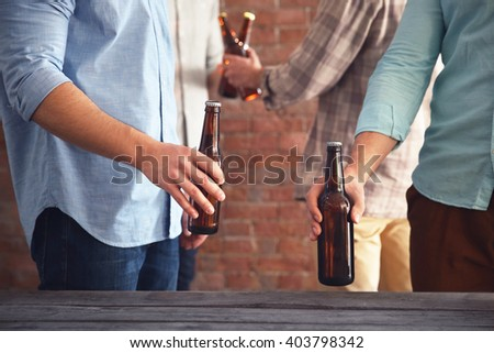 Two men holding glass bottles of beer at the table