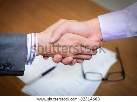 two men holding hands shaking over a business deal contract - stock photo