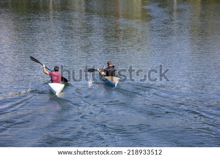 Two men in a canoes, rowing on the tranquil lake  - stock photo