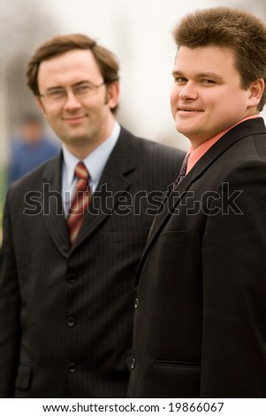 Two men in business suits outdoor portrait