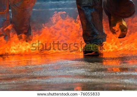 Two men in firefighting suit walking on fire - stock photo