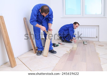 Two men in laid wood floor in white room - stock photo