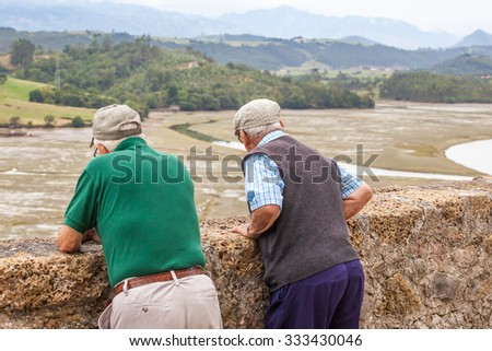 Two men in retirement are looking at the landscape - stock photo