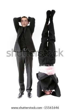 Two men in suits, one upside down - stock photo