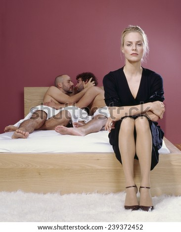 Two Men Kissing Behind a Bored Woman - stock photo