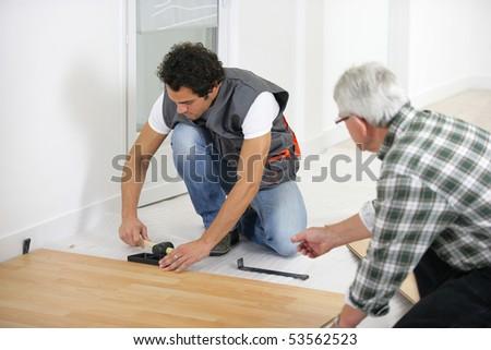 Two men laying parquet - stock photo
