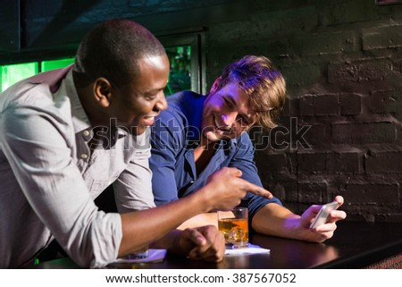 Two men looking at mobile phone and talking while having whiskey at bar counter in bar - stock photo