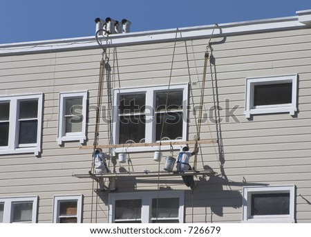 Two men lower themselves the side of an apartment building.