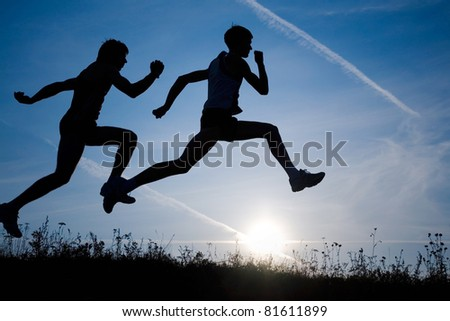 Two men make jog in the field on a sky background by at sunset - stock photo
